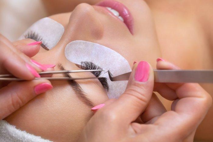 Woman getting eyelash extensions at a lash studio