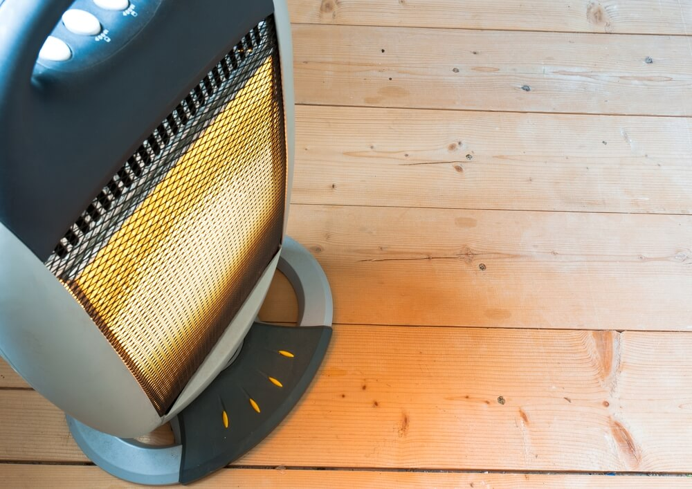An infrared heater sitting on a light wood floor