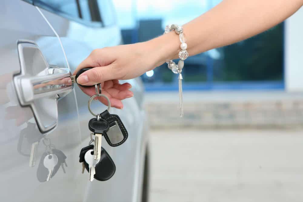 Woman unlocking a car door with a key