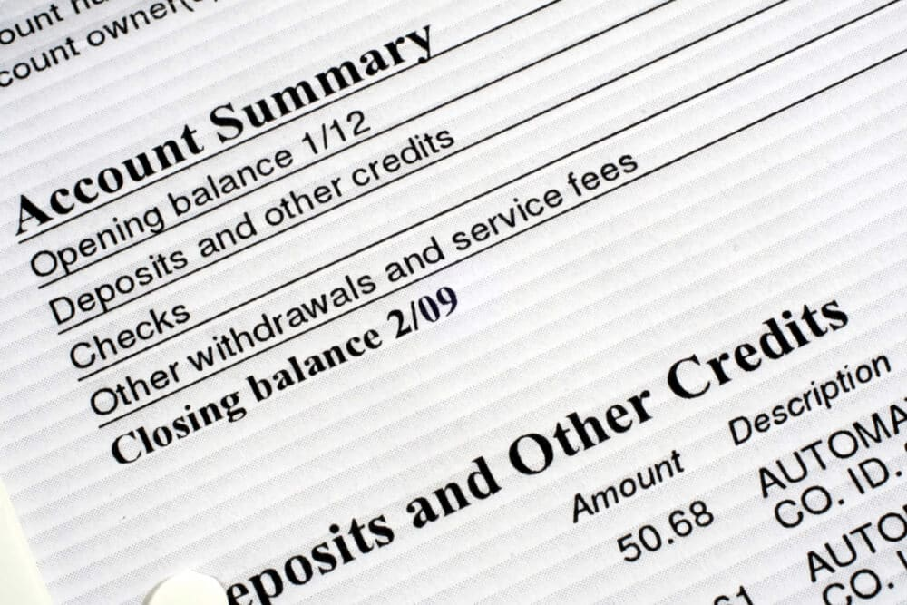 Close-up of a bank account summary showing balance updates and service fees