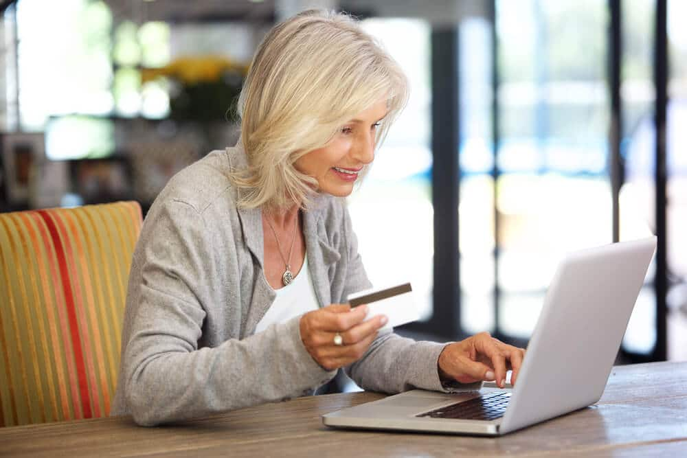 Senior woman using a credit card to shop online
