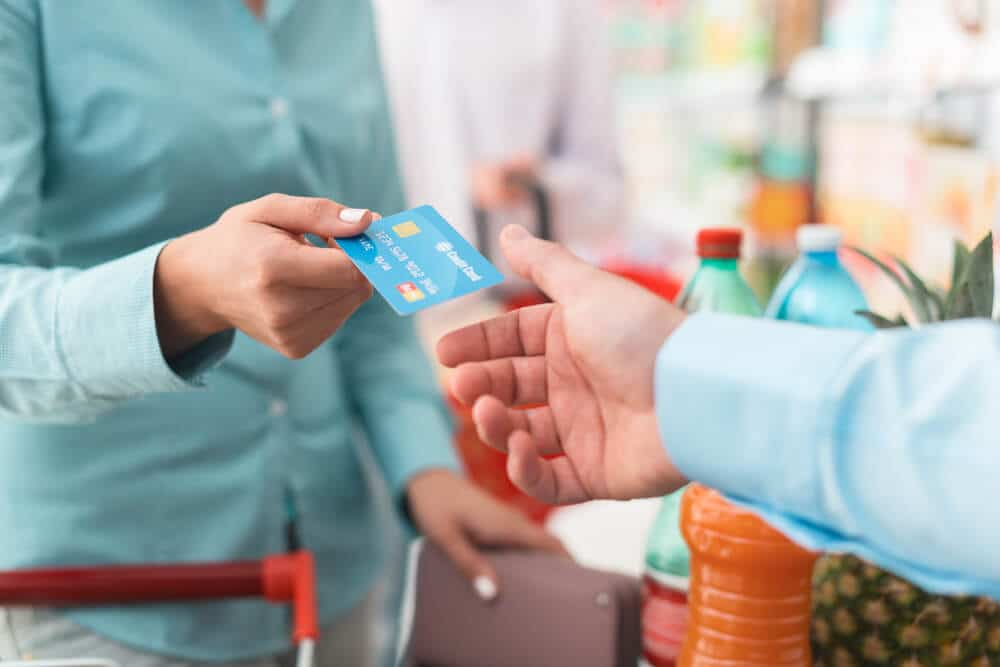 Woman paying for groceries with a credit card