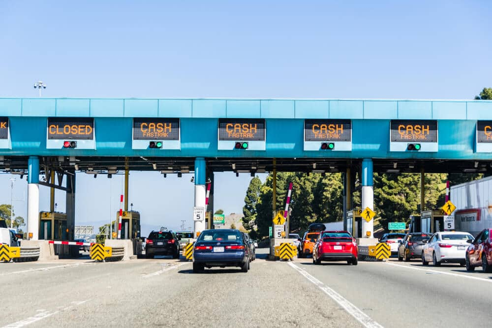 "Cars as they pull up to toll booths. The payment methods are displayed above each lane. ""Cash"" etc is shown."