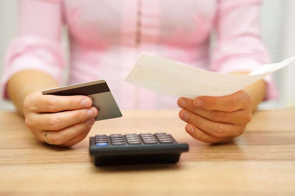 Woman with a credit card, statement, and calculator