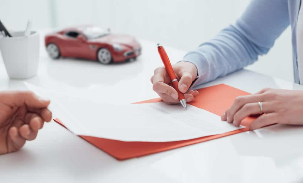 Woman signing car documents