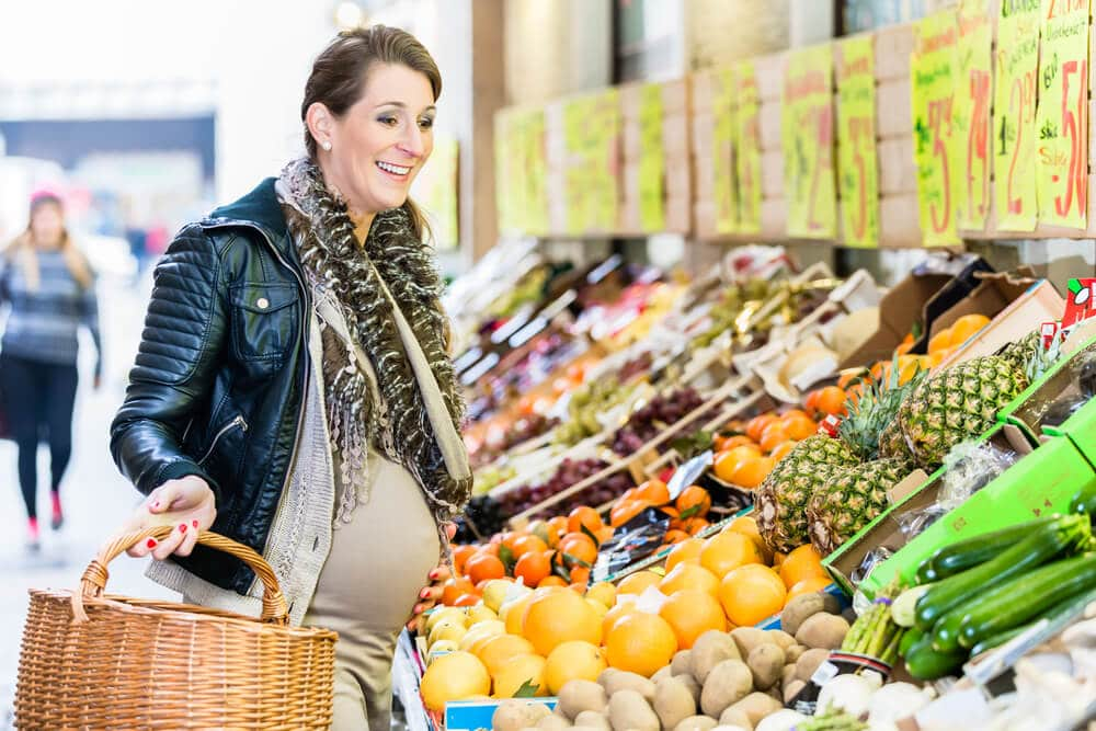 Pregnant woman shopping for produce in a grocery store
