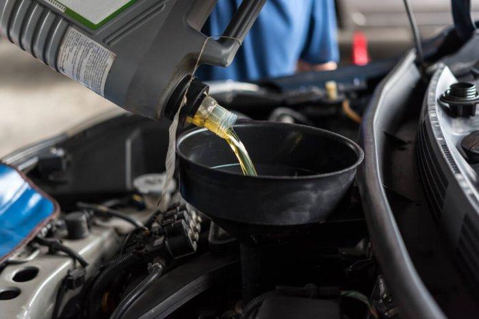 A mechanic pours oil into a car