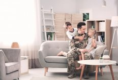 Military service member sitting on couch with his children