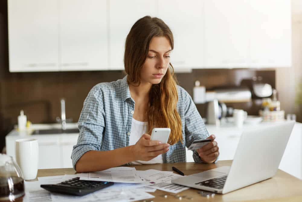 Woman using phone to cancel a pending credit card transaction