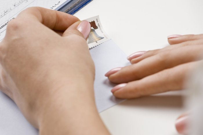 Person placing a stamp to mail a money order