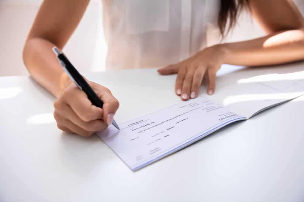 Woman signing a check