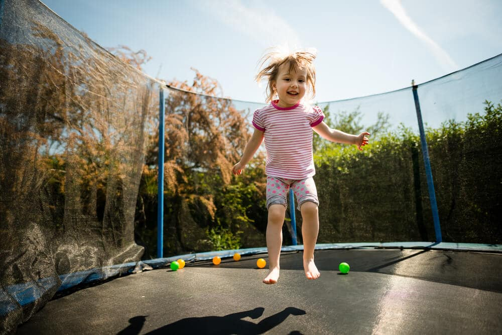 Child jumping on an outdoor trampoline