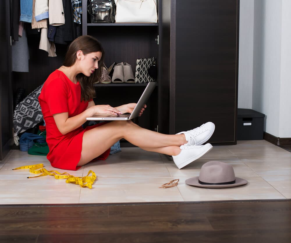 A woman sitting in her closet shopping online for more clothes.