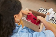 Woman opening a package from an online clothing store