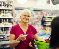 Senior woman paying with a credit card at a grocery store