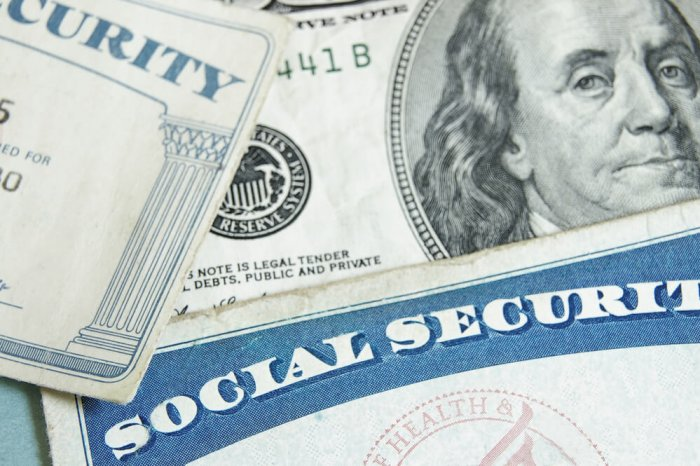 A social security card paying on top of a U.S. bill.