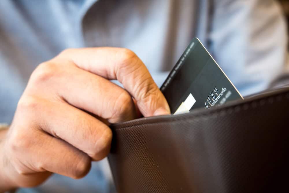 Man placing new prepaid card in wallet