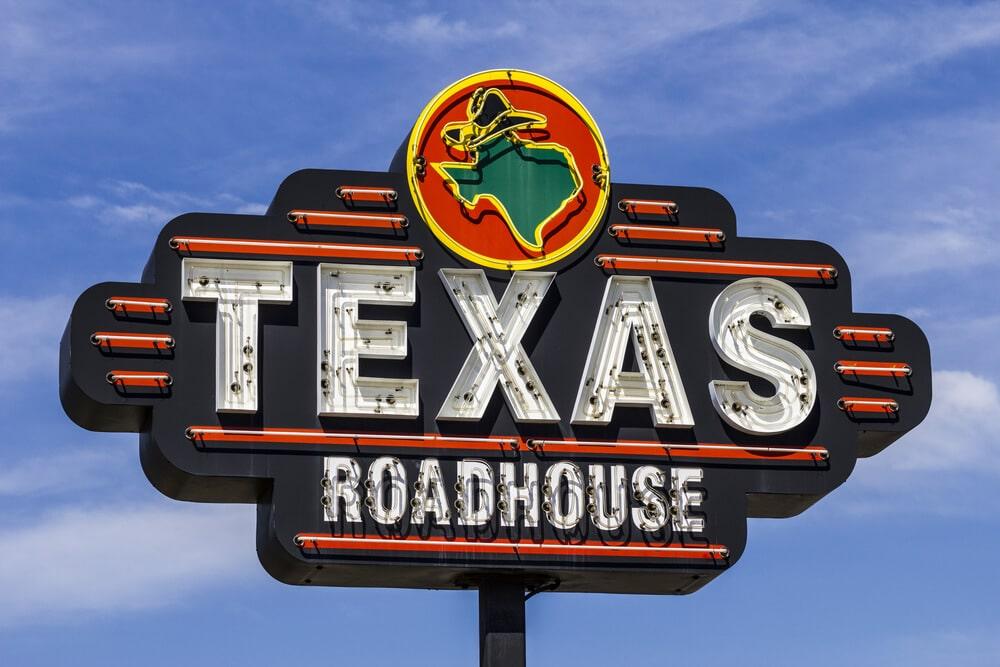 Texas Roadhouse sign against a blue sky