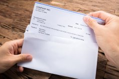 Hands removing a check from an envelope to cash it