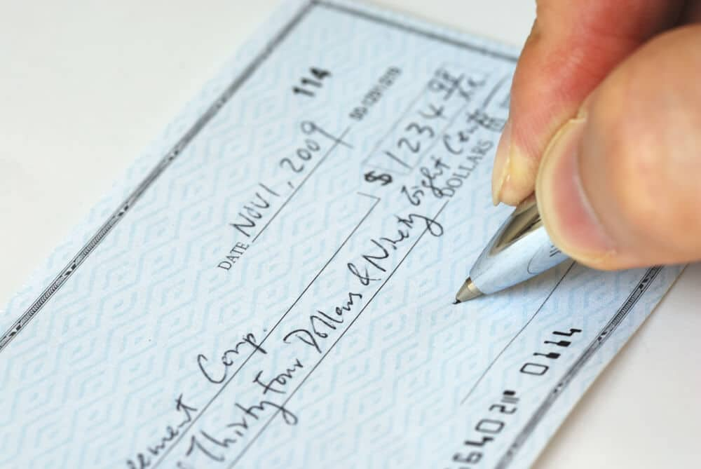 Man's hand signing a filled out personal check