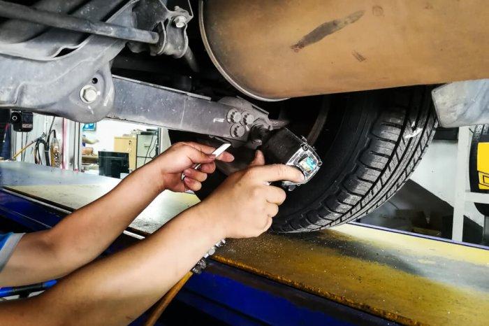 Mechanic adjusting wheel alignment
