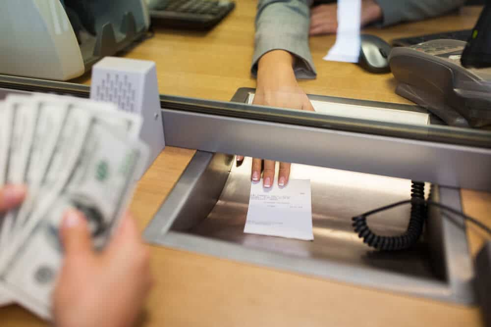 Someone counting cash after cashing their cashier's check at a bank.