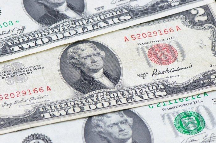 Three two dollar bills on a flat surface