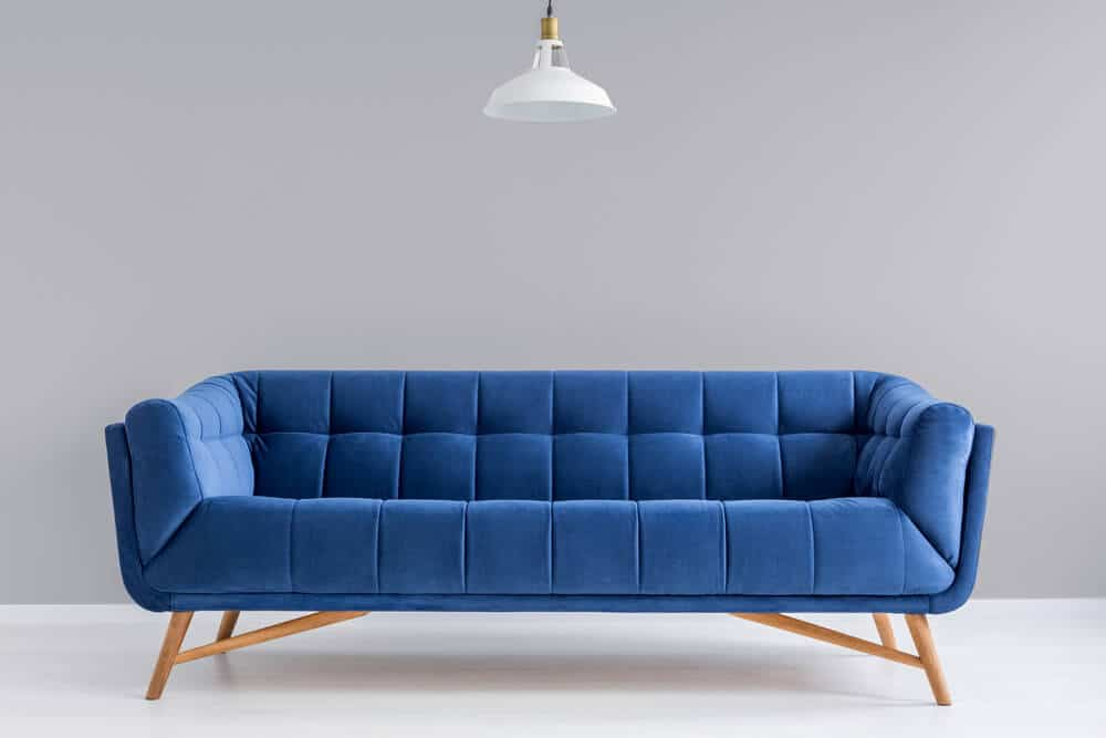 A blue couch with a single light overhead