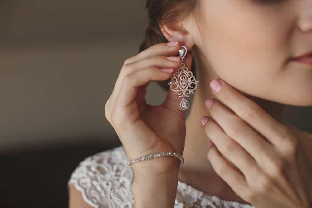 woman putting on drop earrings