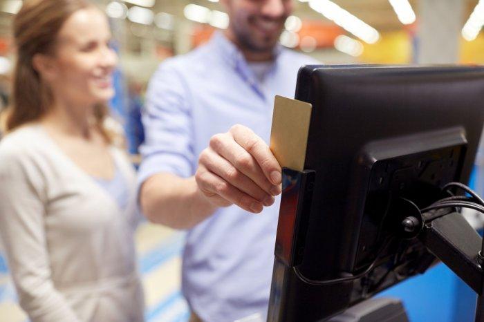 man slides card at self-checkout register