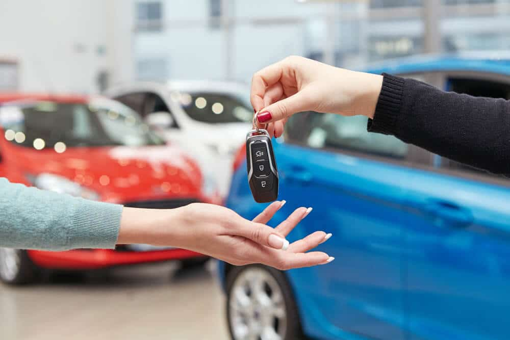 Hands exchange a set of keys; cars in the background