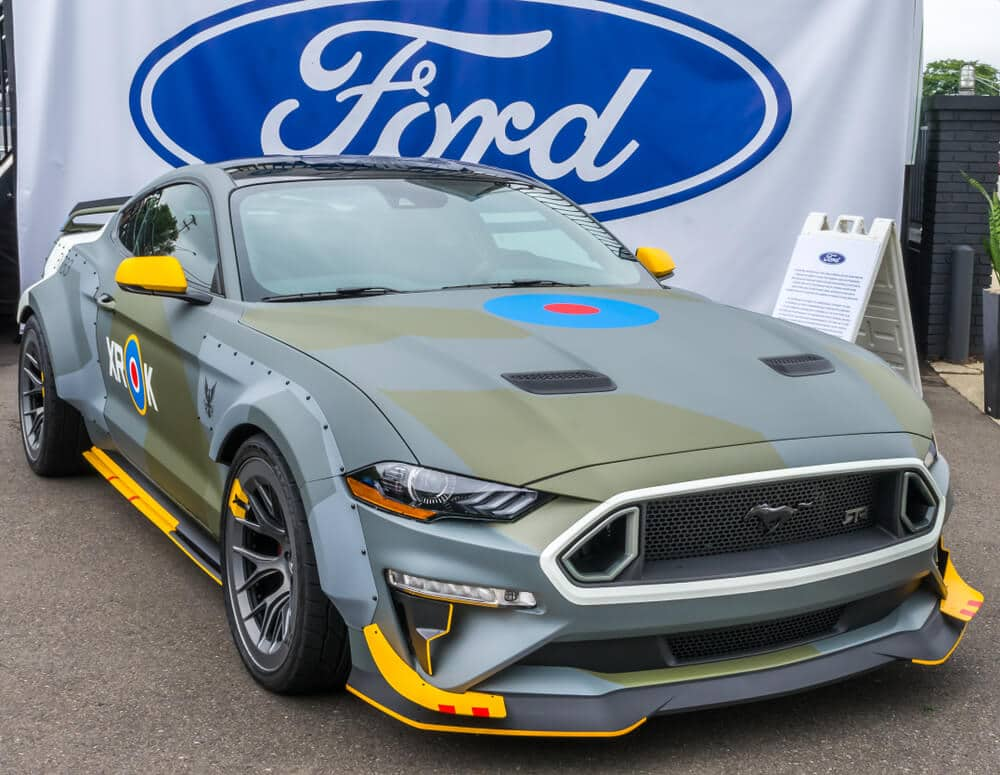 A Ford Mustang wrapped in a matte grey color with yellow accents on the door mirrors, side skirts, and canards.