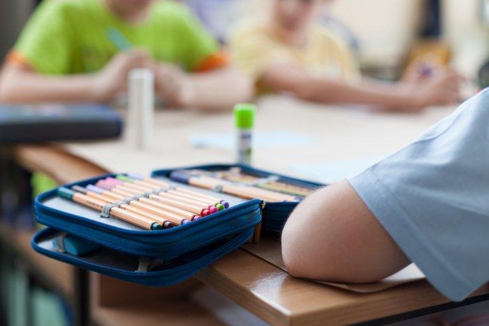 Kids at school using school supplies at their desk