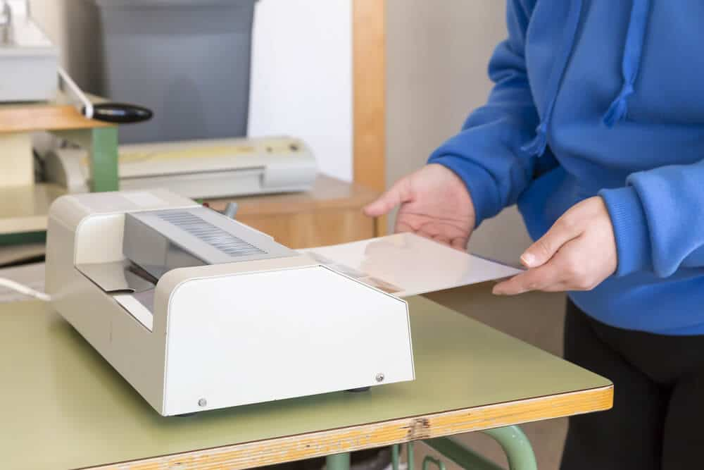 person feeding a document into a standard sized lamination machine